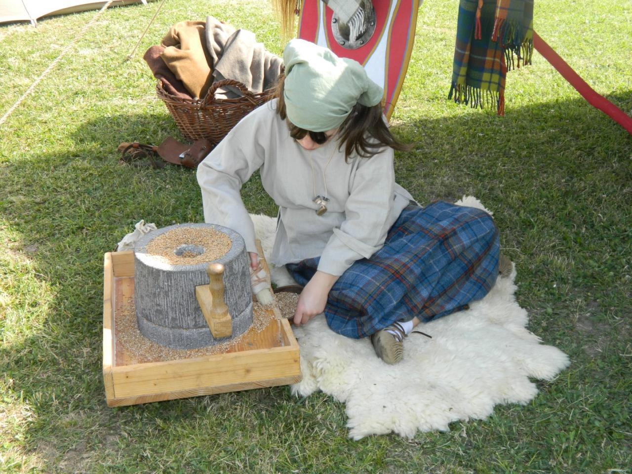 Jeune arverne moulant le blé à l'aide d'une meule
